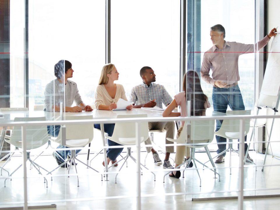 in einem Besprechungsraum sitzen vier Arbeiter und 1 Arbeiter macht Erklärungen an einem Whiteboard