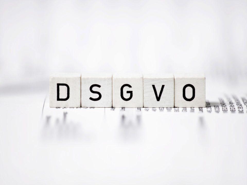 DSGVO steht auf Holzkötzen geschrieben, die auf einen bedruckten Papier stehen